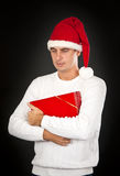 Sad man in a hat Santa with a gift Stock Photography
