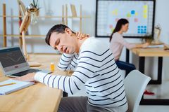 Sad man having pain in neck. Need some rest. Tired male person opening mouth and putting arms on table while keeping eyes closed Royalty Free Stock Photos