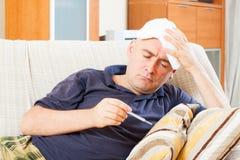 Sad man having temperature Stock Images
