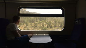 Sad man in headphones looking out window train stock footage