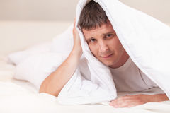Sad man hiding in bed under sheets. Royalty Free Stock Photo