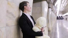 Sad man with a toy bear. Sad man is holding a bear toy in his hands, he is waiting for his beloved woman stock video footage