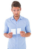 Sad man holding a broken card. On white background Stock Images