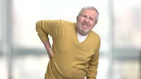 Sad man holding hand on sick back. Elderly man suffering from pain in lower back on blurred background stock footage
