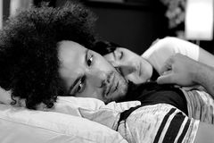 Sad man holding hand of sleeping girlfriend expressing problem in relationship black and white Stock Images