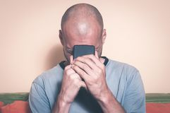 Sad man holding his cell phone in his hands and cry because his girlfriend break up with him over the text message Stock Photography