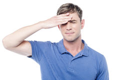 Sad man holding his forehead with his hand Stock Photo