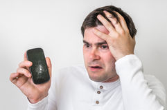 Sad man is holding mobile phone with broken screen. Sad man is holding mobile phone in his hand with broken screen royalty free stock images