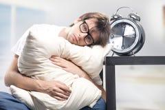 Sad man holding pillow. And the clock Stock Photos