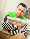 Sad man at home. Unhappy man sitting on sofa at home stock photo