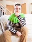 Sad man at home. Unhappy man on sofa at home stock photo