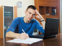 Sad man with laptop and documents. Sad man with laptop and financial documents Stock Images