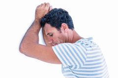 Sad man leaning his head against a wall Stock Images