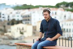 Sad man listening to music on a ledge. With a town in the background royalty free stock photo