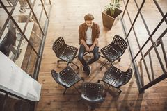 Sad man locating opposite unoccupied places. Top view full length portrait of unhappy bearded male sitting opposite empty chairs indoor. Loneliness concept Stock Photography