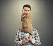 Sad man with long neck. Coiled scarf over dark background Stock Image