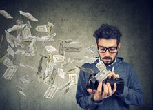 Hipster man looking at his wallet with money dollar banknotes flying out away. Sad man looking at his wallet with money dollar banknotes flying out away Stock Photos