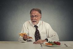 Sad man looking at pizza tired of salad diet Royalty Free Stock Photo