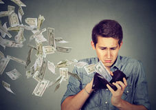 Sad man looking at wallet with money dollars flying away. Sad man looking inside wallet with money dollar banknotes flying out away Stock Image