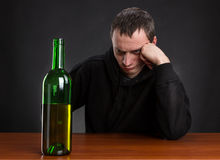 Sad man looks at the bottle Royalty Free Stock Photo