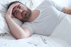 Sad man lying in the bed Stock Photography