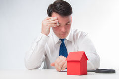 Sad Man with a magnifying glass and paper house Royalty Free Stock Image