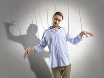 Sad man on manipulating ropes with shadow of puppeteer behind  on grey. Portrait of sad man on manipulating ropes with shadow of puppeteer behind  on grey Royalty Free Stock Photos