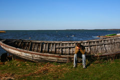 Sad man near the old wooden boat. One young sad man sitting on the big lonely old boat near the Baltic Sea on island Saaremaa in Estonia stock photos