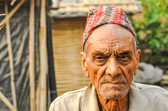 Sad man in Nepal. Damak, Nepal - circa May 2012: Old man with wrinkled face with cap on his head frowns and looks sadly to photocamera at Nepali refugee camp in stock photo