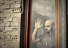 Sad man. Man with nostalgia looking out the window Stock Photos