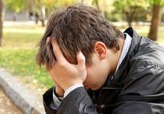 Sad Man outdoor. Sad Young Man sit in the Autumn Park Stock Photos