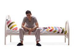Sad man in pajamas sitting on a bed Royalty Free Stock Image