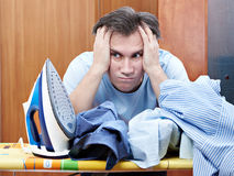 Sad man with pile of crumpled shirts and iron Royalty Free Stock Photo