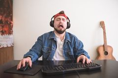 Sad man plays a video game at home behind a computer in a cozy room stock photography