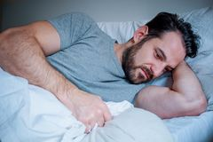 Sad man portrait lying in his bed at home stock images