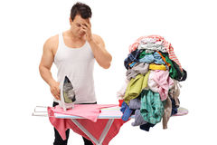 Sad man posing next to a pile of clothes Royalty Free Stock Photo