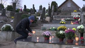 Sad man put two candle on black marble tombstone in cemetery. 4K