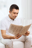Sad man reading newspaper at home Royalty Free Stock Photo