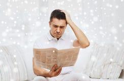 Sad man reading newspaper at home Royalty Free Stock Photo