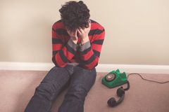 Sad man receiving bad news on telephone Stock Photos