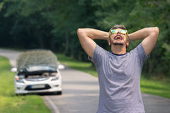 Sad man on the road next to the broken car. Stressed and frustrated driver pulling his hair while standing on the road next to broken car. Road trip problems and Royalty Free Stock Image