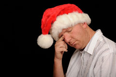 Sad man in Santa hat. A studio view of a weeping man wearing a white casual shirt and a red Santa hat, wiping a tear from his eye Stock Images