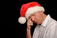 Sad man in Santa hat Stock Images