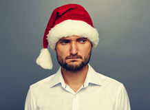 Sad man in santa hat over dark Royalty Free Stock Photo