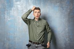 Sad man showing his empty pockets. On grunge background Royalty Free Stock Photography