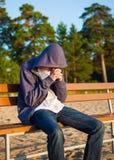 Sad Young Man outdoor. Sad Man sit on the Bench outdoor Stock Photo
