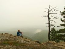 Sad man sit on the peak of sandstone rock and watching over the misty and foggy morning valley. Royalty Free Stock Images