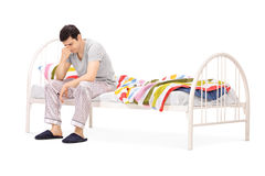 Sad man sitting on a bed and contemplating. Isolated on white background Royalty Free Stock Image