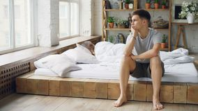 Sad man sitting on bed after quarrel with his wife touching his face and looking at window while his wife is lying in. Sad man is sitting on bed after quarrel stock video