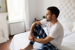 Sad man sitting on bed thinking about problems Stock Photos